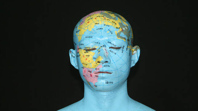 Image: Photograph of a man's face painted with a world map